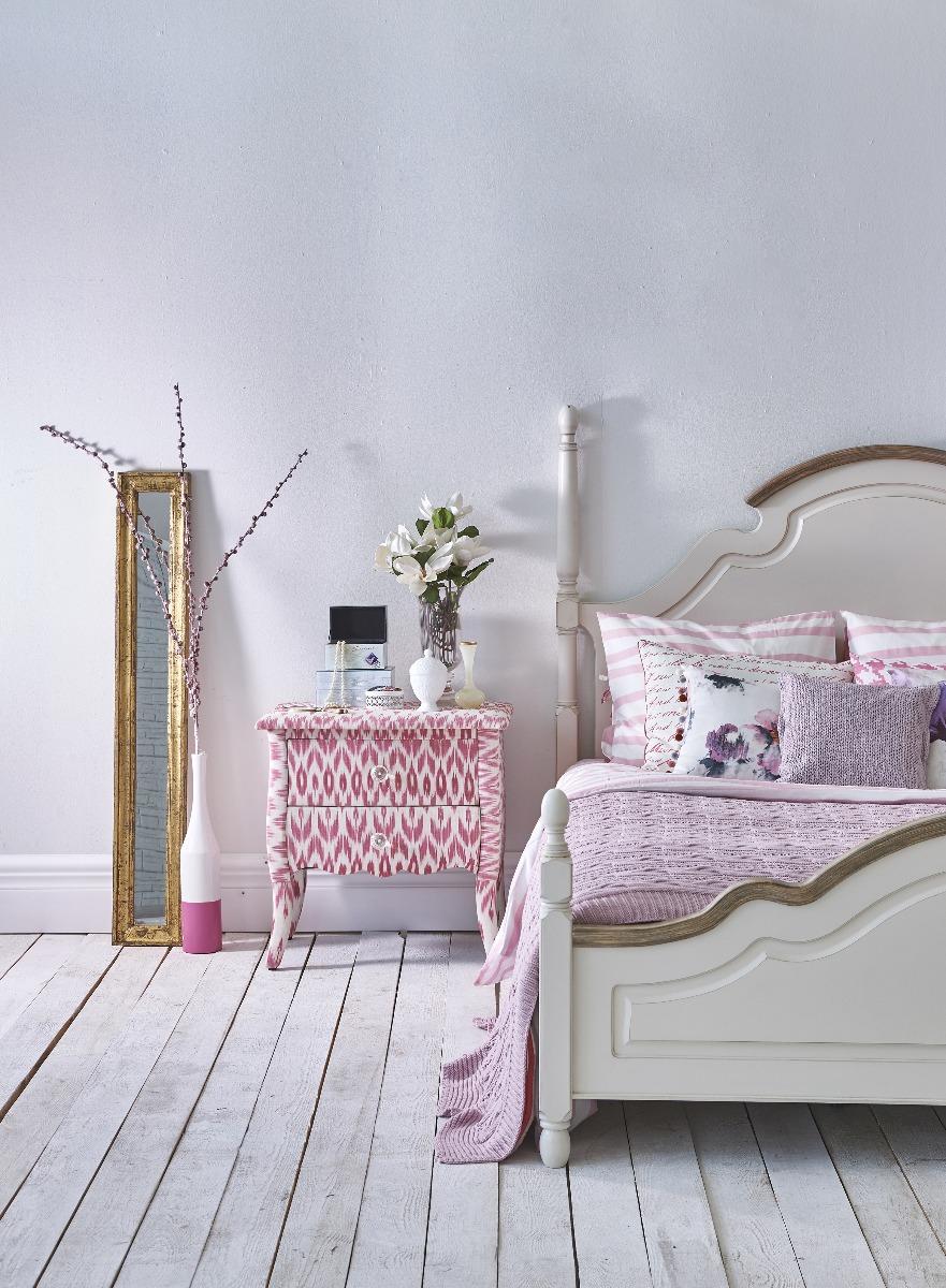 Das Bild zeigt ein Schlafzimmer im Landhausstil mit Farbakzenten.