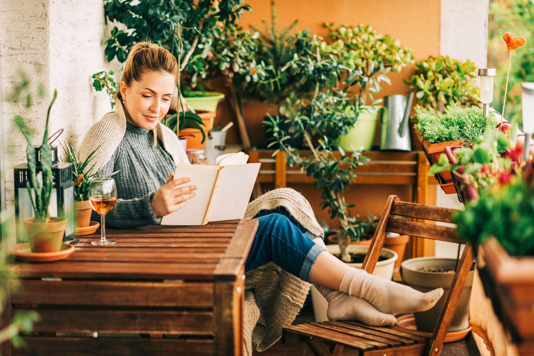 Das Bild zeigt Gartenmöbel aus Holz und eine junge Frau.