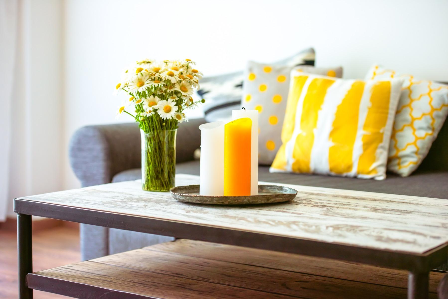 Das Bild zeigt einen Wohnzimmertisch mit Blumen.